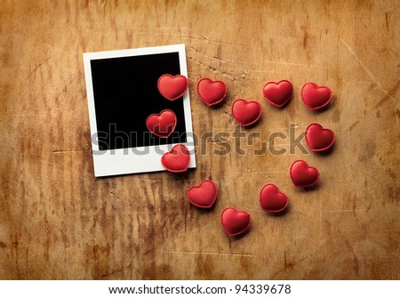 Blank instant photo and small red hearts lying in the shape of a heart on old dark grunge background.