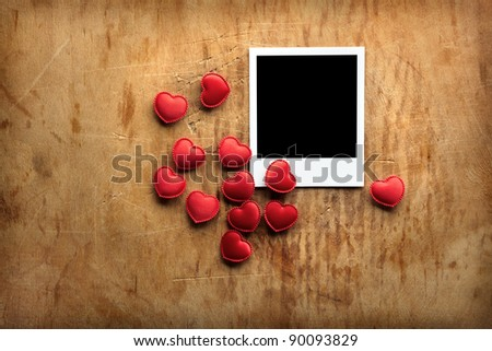 Blank instant photo and small red hearts on old dark grunge background. - stock photo