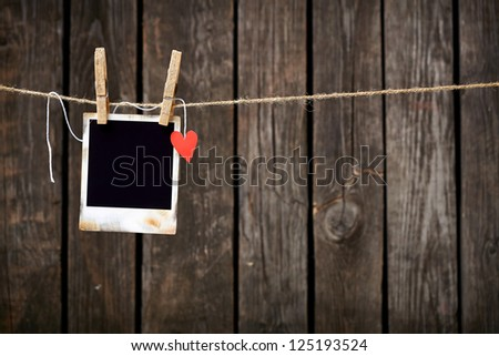 Blank instant photo and small red paper heart hanging on the clothesline. On old wood background. - stock photo