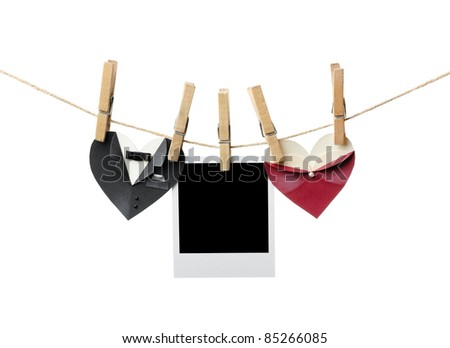 Blank instant photo between symbolic male and female heart shapes hanging on the clothesline. Isolated on white. Wedding or st.Valentine theme.