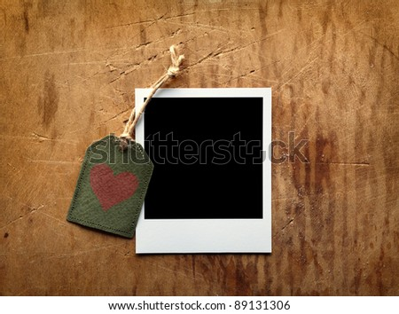Blank instant photo frame and vintage gift tag with red heart shape on old wooden background. - stock photo