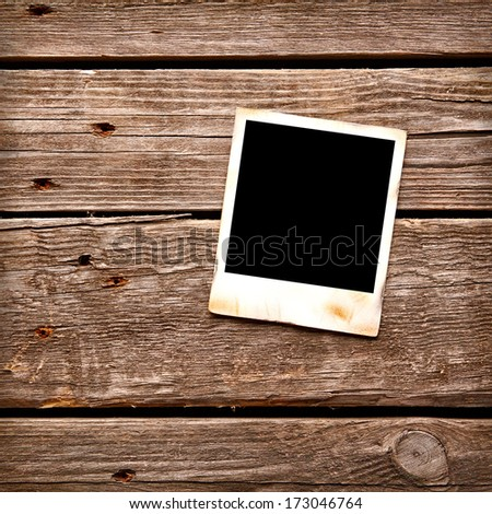 Blank instant photo frame on old wooden background. - stock photo
