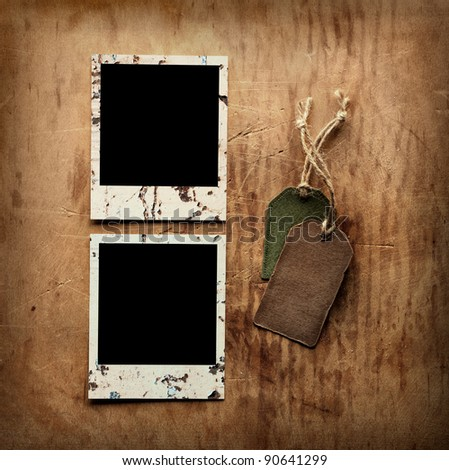 Blank instant photo frames and vintage blank gift tags on old wooden background. - stock photo