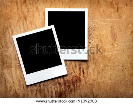 Blank instant photo frames on old wooden background. - stock photo