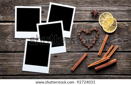 Blank instant photo frames with coffee beans in shape of a heart and cinnamon sticks on old wooden background. - stock photo