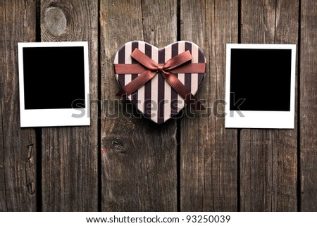 Blank instant photo frames with heart shaped Valentines Day gift box on old wooden background. - stock photo