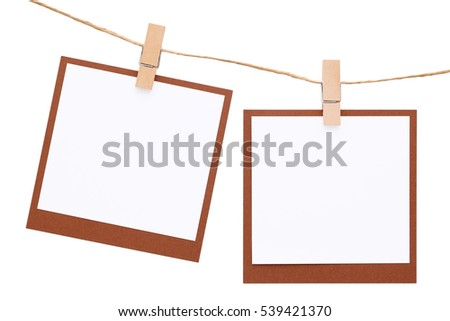 Blank instant photo hung on rope with clothespin isolated on white background