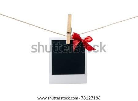 Blank instant photo with small red satin bow hanging on the clothesline. Isolated on white. - stock photo