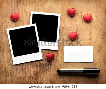 Blank instant photos and small red hearts with blank business (visit) card and fountain pen on old dark grunge background. Romantic theme. - stock photo
