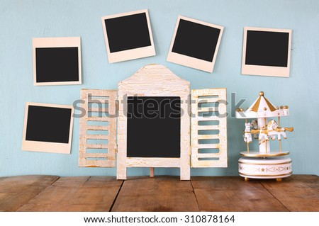 blank instant photos hang over wooden textured background next to blank blackboard  and vintage white carousel horses - stock photo