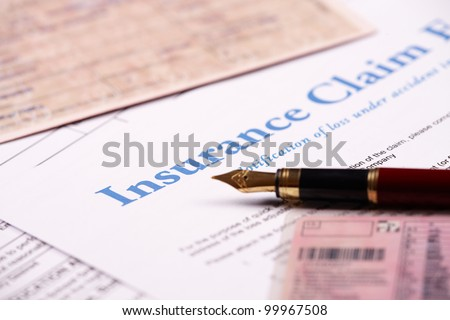 Blank insurance claim form and other papers like ID or vehicle documents and pen lying on desk - stock photo