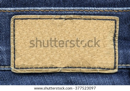 blank jeans light brown  leather label on blue jeans background