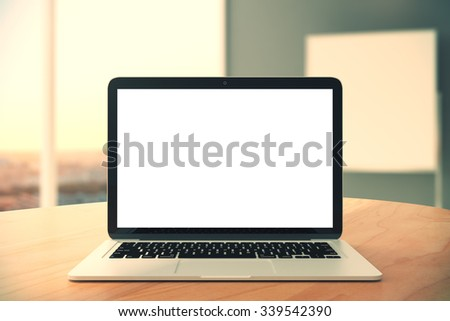 Blank laptop screen on wooden table in the office, mock up - stock photo