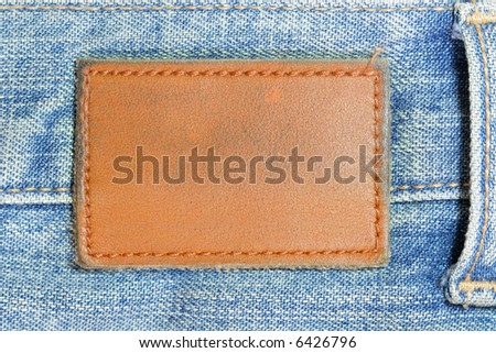 Blank lather label on blue jeans - stock photo