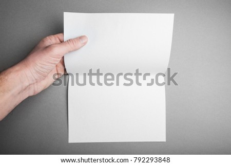 Blank layout open sheet folded 2 times in a hand of a man with soft shadows on a gray background for design.