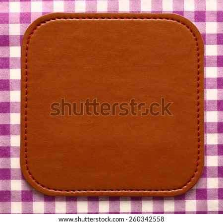 Blank leather brown label on checked background