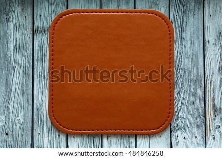 Blank leather brown label on wooden background