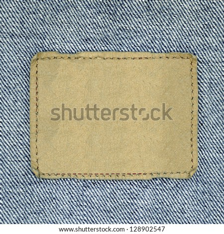Blank leather jeans label sewed on a blue jeans. Can be used as background for your text.
