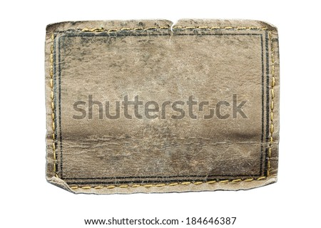 Blank leather jeans label sewed on a blue jeans isolated on white background with clipping path