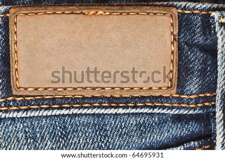 Blank leather label on blue jeans - stock photo