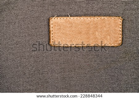 Blank Leather Label Tag on cotton fabric material texture background.
