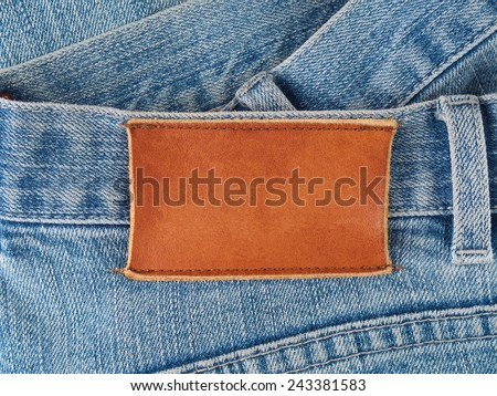 Blank leather patch sewed to old denim jeans