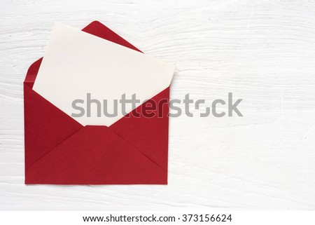 Blank letter paper with red envelop on white wooden desk - stock photo