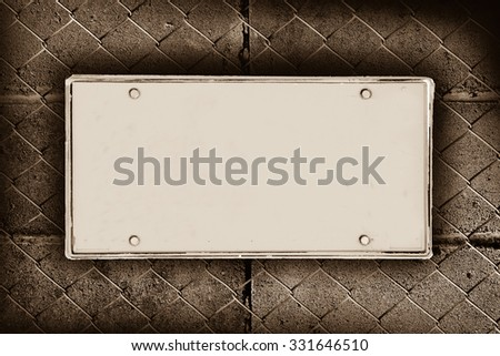 blank license plate on block wall and net fence background ,vintage tone - stock photo