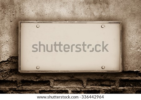 blank license plate on cracked brick wall ,vintage tone - stock photo