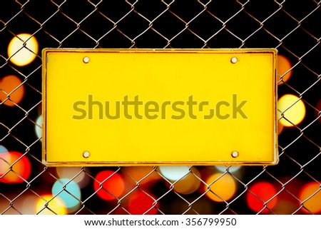 blank license plate on net fence and blur bokeh from traffic light background
