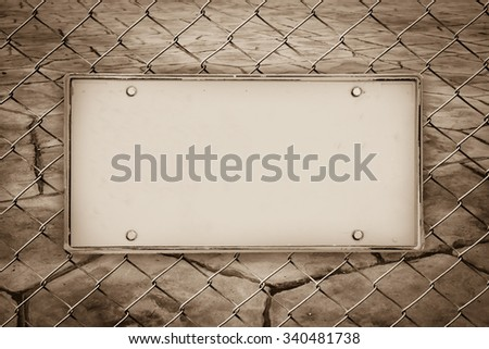 blank license plate on net fence with blur perspective old stone floor background - stock photo