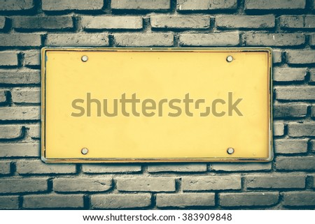 blank license plate on old dirty brick wall - stock photo