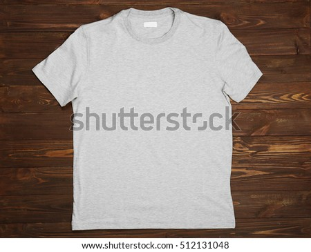Blank light grey t-shirt on wooden background