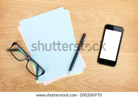 Blank lined paper with mobile phone, office supplies and glasses on wooden table. Above view - stock photo