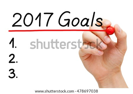 Blank list of goals for year 2017 isolated on white. Hand underlining 2017 Goals with red marker on transparent wipe board.