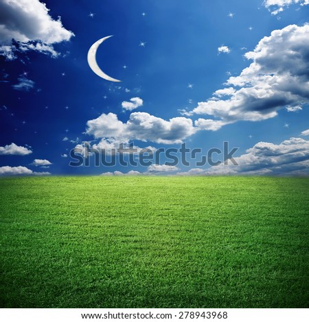 Blank meadow under early evening sky with moon and stars - stock photo