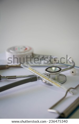 Blank medical clipboard with stethoscope and thermometer - stock photo