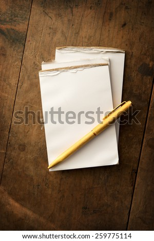 Blank memo pad and gold pen on old grungy wooden surface with dim lighting. Intentionally shot and with low key shadows - stock photo