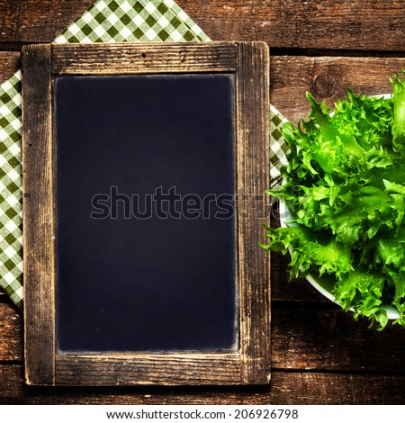 Blank menu blackboard over vintage wooden background with green fresh salad in a bowl. - stock photo