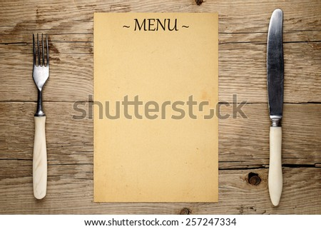 Blank menu, fork and knife on old wooden background - stock photo