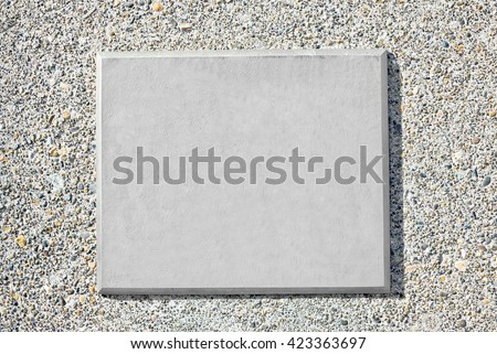 Blank metal plaque mounted on an old concrete wall.