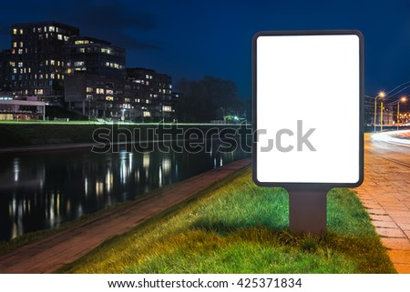 Blank mock up of vertical street ad lightbox on city background at night