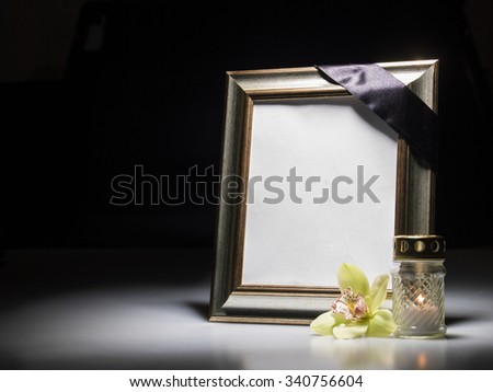 Blank mourning frame for sympathy card on dark background - stock photo