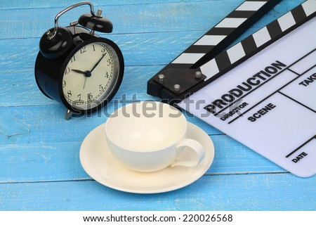 Blank movie clapper board with coffee and classic clock - stock photo