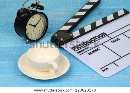 Blank movie clapper board with coffee cup and clock, slate film. - stock photo