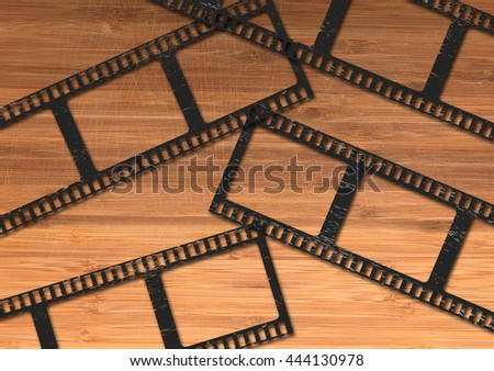 Blank movie or photography film strip lying on the wooden desk - stock photo