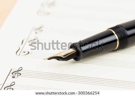 Blank music score on cream color paper with pen - stock photo