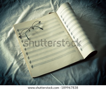 Blank musical composition sheet music and eyeglasses - stock photo