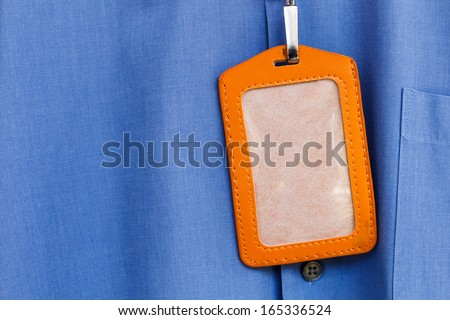 Blank name leather badge on blue shirt background - stock photo
