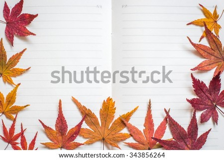 Blank note book paper texture line pattern background for handwriting with colorful red orange yellow autumn leaves frame: Natural dry autumn leaves on empty textured horizontal line for copyspace  - stock photo